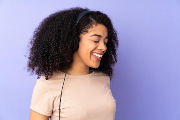 Jonge afro-amerikaanse vrouw geïsoleerd op paarse muziek luisteren