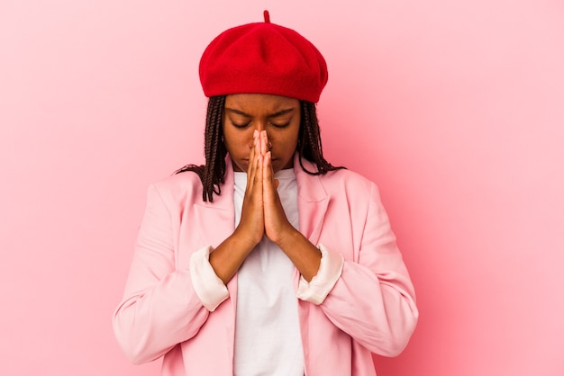 Jonge afro-amerikaanse vrouw geïsoleerd op roze achtergrond bidden, tonen toewijding, religieuze persoon op zoek naar goddelijke inspiratie.