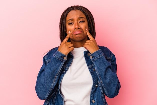Jonge afro-amerikaanse vrouw geïsoleerd op roze achtergrond huilen, ongelukkig met iets, pijn en verwarring concept.