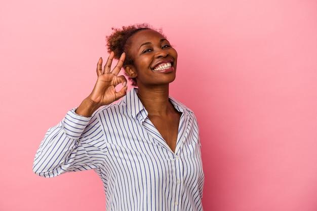 Jonge afro-amerikaanse vrouw geïsoleerd op roze achtergrond knipoogt en houdt een goed gebaar met de hand.