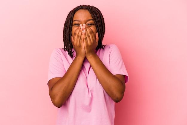 Jonge afro-amerikaanse vrouw geïsoleerd op roze achtergrond lachen om iets, mond bedekken met handen.