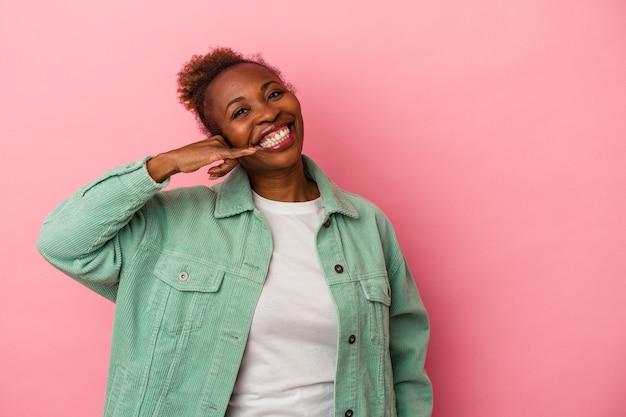Jonge afro-amerikaanse vrouw geïsoleerd op roze achtergrond met een mobiel telefoongesprek gebaar met vingers.
