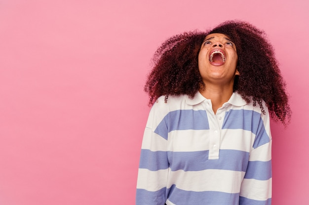 Jonge afro-amerikaanse vrouw geïsoleerd op roze achtergrond schreeuwen erg boos, woede concept, gefrustreerd.