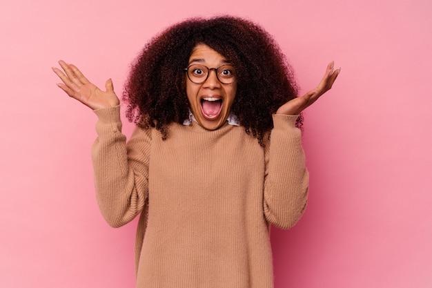 Jonge afro-amerikaanse vrouw geïsoleerd op roze die een overwinning of succes viert, hij is verrast en geschokt.