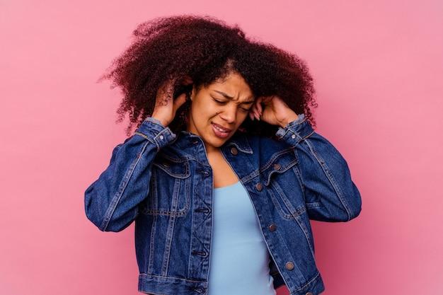 Jonge afro-amerikaanse vrouw geïsoleerd op roze die oren bedekt met vingers, gestrest en wanhopig door een luid ambient.