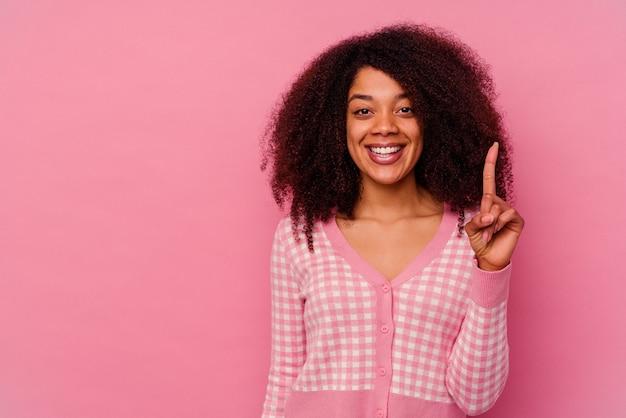 Jonge afro-amerikaanse vrouw geïsoleerd op roze met nummer één met vinger.