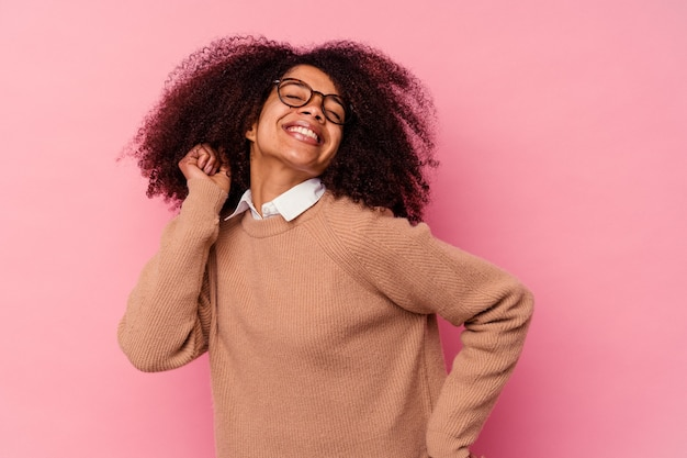 Jonge afro-amerikaanse vrouw geïsoleerd op roze muur dansen en plezier maken.