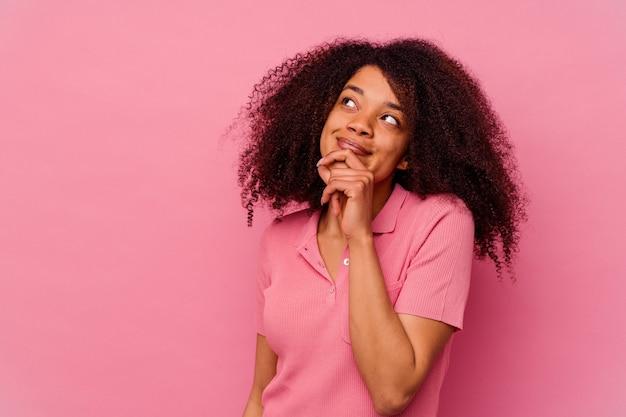 Jonge afro-amerikaanse vrouw geïsoleerd op roze ontspannen denken over iets kijken naar een kopie ruimte.
