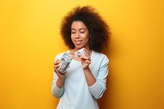 Jonge afro-amerikaanse vrouw geld steken in glazen pot. besparingen concept
