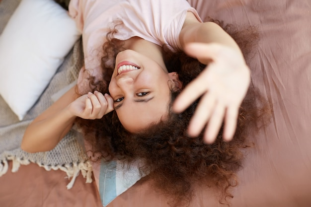 Jonge afro-amerikaanse vrouw geniet van de zonnige dag thuis en lacht, brengt ze vrije dag door en rust thuis, liggend op het bed.