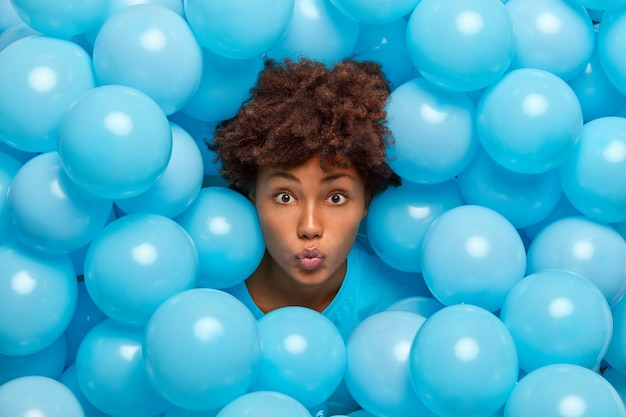 Jonge afro-amerikaanse vrouw houdt lippen afgeronde poses rond blauwe opgeblazen ballonnen tijdens een feestelijke gebeurtenis