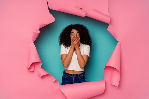 Jonge afro-amerikaanse vrouw in gescheurd papier geïsoleerd op blauwe achtergrond geschokt die mond met handen bedekken.