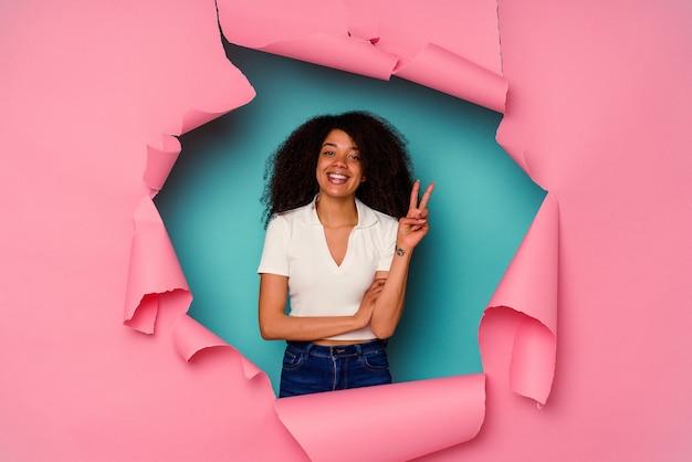 Jonge afro-amerikaanse vrouw in gescheurd papier geïsoleerd op blauwe muur met nummer twee met vingers.