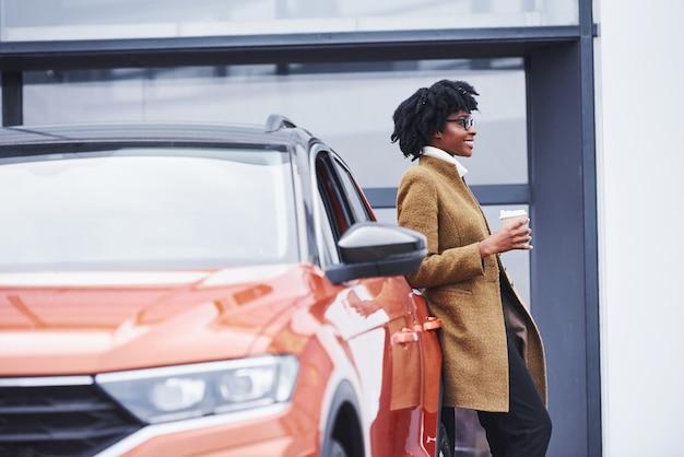 Jonge afro-amerikaanse vrouw in glazen en met kopje drank staat buiten in de buurt van moderne auto.