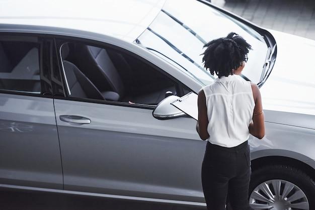 Jonge afro-amerikaanse vrouw in glazen en met notitieblok staat in de autosalon in de buurt van het voertuig.