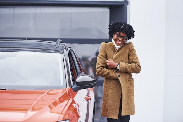 Jonge afro-amerikaanse vrouw in glazen staat buiten in de buurt van moderne auto.