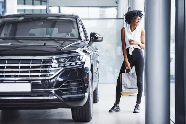 Jonge afro-amerikaanse vrouw in glazen staat in autosalon in de buurt van voertuig met pakket in handen.