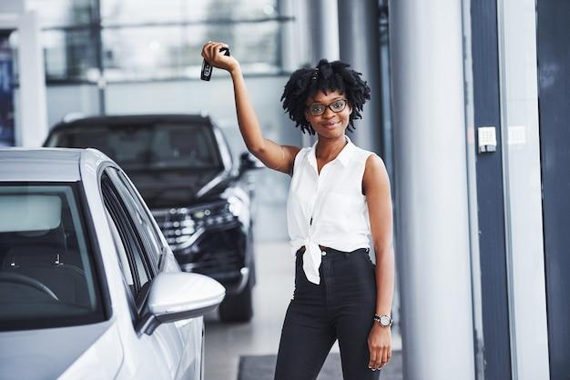 Jonge afro-amerikaanse vrouw in glazen staat in de autosalon in de buurt van voertuig met sleutels in handen.