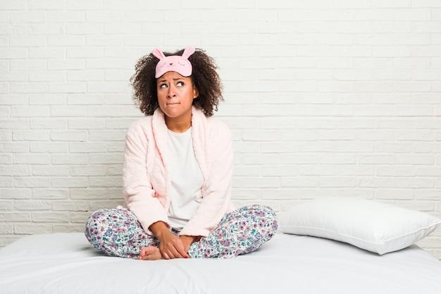 Jonge afro-amerikaanse vrouw in het bed verward pijama draagt, voelt zich twijfelachtig en onzeker.