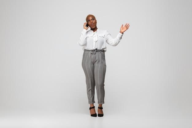 Jonge afro-amerikaanse vrouw in kantoorkleding op grijs
