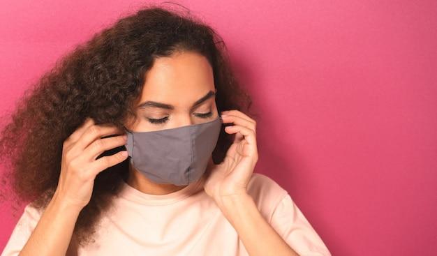 Jonge afro-amerikaanse vrouw in licht peachy t-shirt zetten herbruikbare gezichtsmasker
