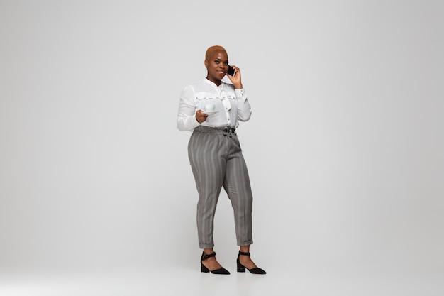 Jonge afro-amerikaanse vrouw in vrijetijdskleding op grijs