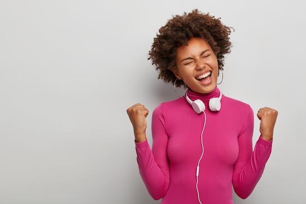 Jonge afro-amerikaanse vrouw juicht succes toe, staat in gelukkige triomferende pose in de studio