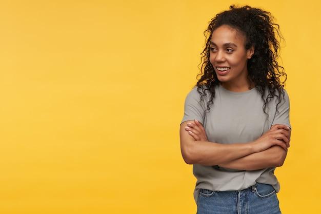 Jonge afro-amerikaanse vrouw lacht, draagt grijs t-shirt en spijkerbroek, houdt haar handen gekruist