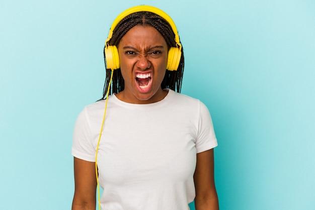 Jonge afro-amerikaanse vrouw luisteren naar muziek geïsoleerd op blauwe achtergrond schreeuwen erg boos en agressief.