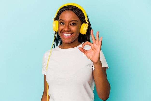 Jonge afro-amerikaanse vrouw luisteren naar muziek geïsoleerd op blauwe achtergrond vrolijk en zelfverzekerd met ok gebaar.