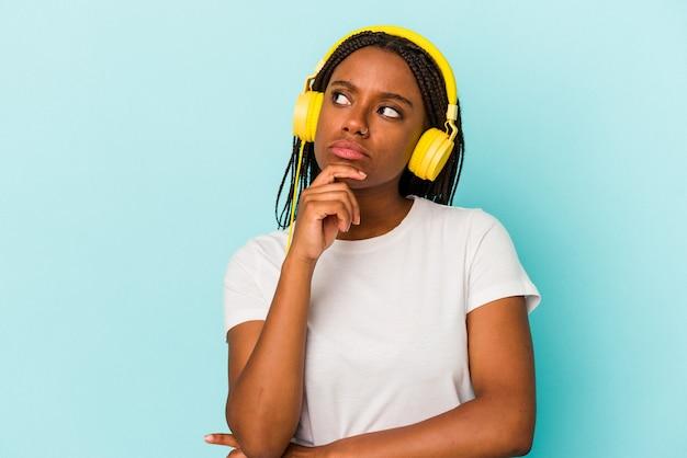 Jonge afro-amerikaanse vrouw luisteren naar muziek geïsoleerd op blauwe achtergrond zijwaarts kijkend met twijfelachtige en sceptische uitdrukking.