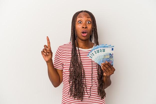 Jonge afro-amerikaanse vrouw met bankbiljetten geïsoleerd op een witte achtergrond met een geweldig idee, concept van creativiteit.