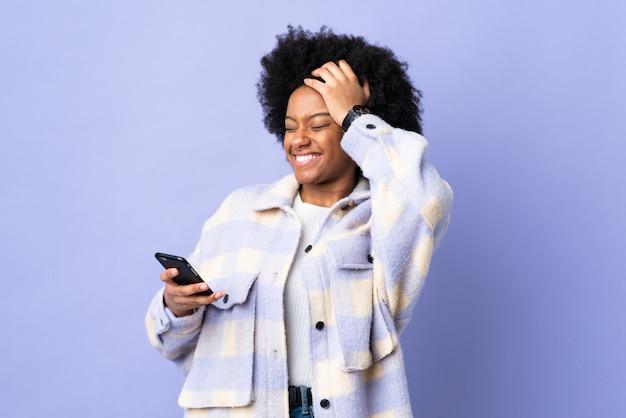 Jonge afro-amerikaanse vrouw met behulp van mobiele telefoon geïsoleerd op paarse achtergrond heeft iets gerealiseerd en van plan de oplossing
