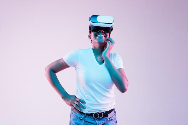 Jonge afro-amerikaanse vrouw met behulp van vr-bril in neonlicht