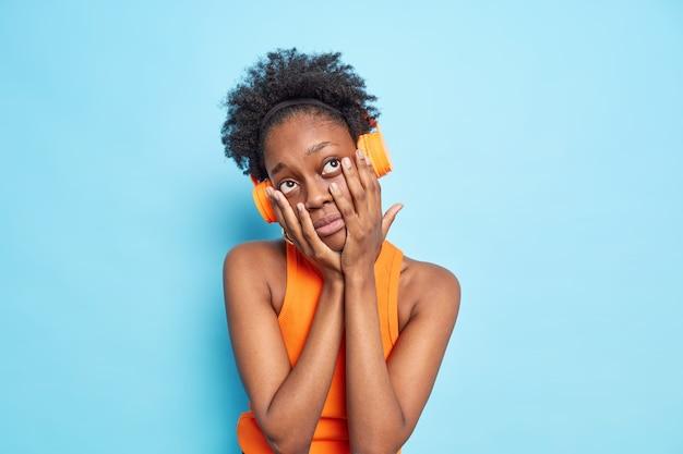Jonge afro-amerikaanse vrouw met donkere huidskleur en krullend haar voelt zich verveeld, houdt haar handen op het gezicht luistert naar muziek via een koptelefoon