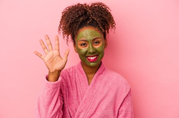 Jonge afro-amerikaanse vrouw met een badjas en gezichtsmasker geïsoleerd op een roze achtergrond die vrolijk lacht en nummer vijf met vingers toont.