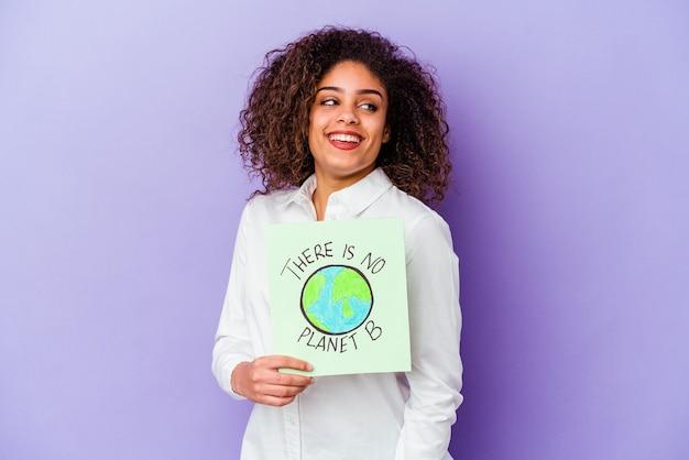 Jonge afro-amerikaanse vrouw met een bordje er is geen planeet b geïsoleerd kijkt opzij glimlachend, vrolijk en aangenaam.
