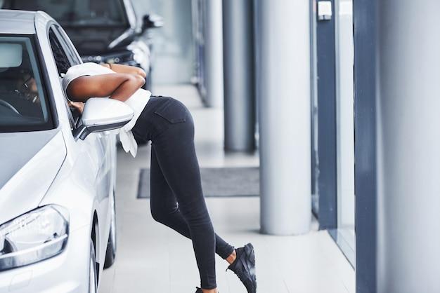 Jonge afro-amerikaanse vrouw met een bril staat in de autosalon in de buurt van het voertuig.