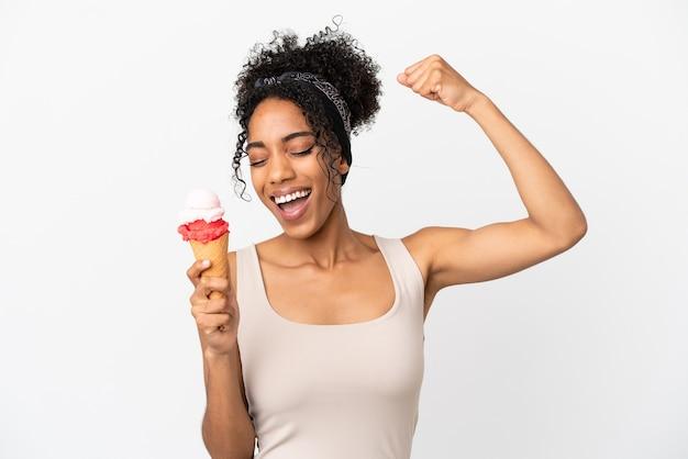 Jonge afro-amerikaanse vrouw met een cornet-ijs geïsoleerd op een witte achtergrond die een overwinning viert
