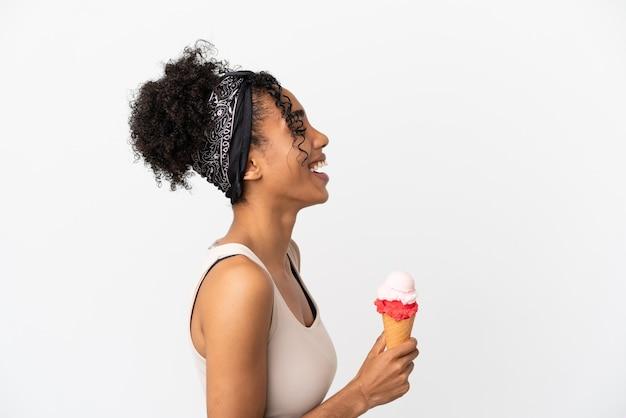 Jonge afro-amerikaanse vrouw met een cornet-ijs geïsoleerd op een witte achtergrond lachend in zijpositie