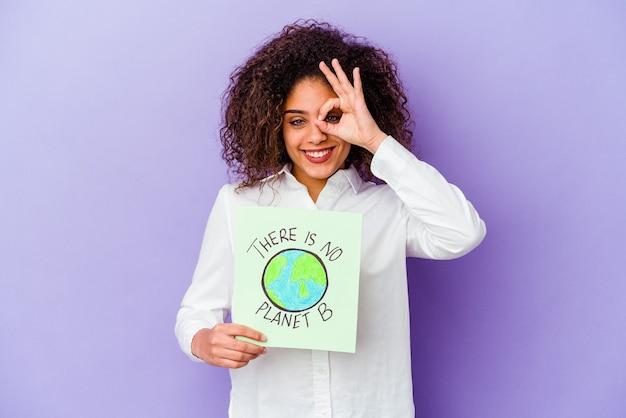 Jonge afro-amerikaanse vrouw met een er is geen planeet b-plakkaat geïsoleerd opgewonden houden ok gebaar op oog.