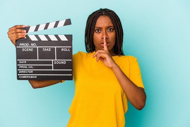 Jonge afro-amerikaanse vrouw met een filmklapper geïsoleerd op een blauwe achtergrond die een geheim houdt of om stilte vraagt.