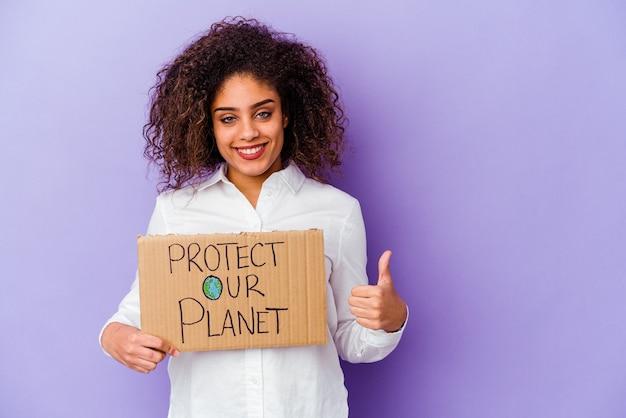 Jonge afro-amerikaanse vrouw met een girl power plakkaat geïsoleerd op een paarse achtergrond glimlachend en duim omhoog
