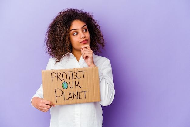 Jonge afro-amerikaanse vrouw met een girl power plakkaat geïsoleerd op paarse achtergrond zijwaarts kijkend met twijfelachtige en sceptische uitdrukking.