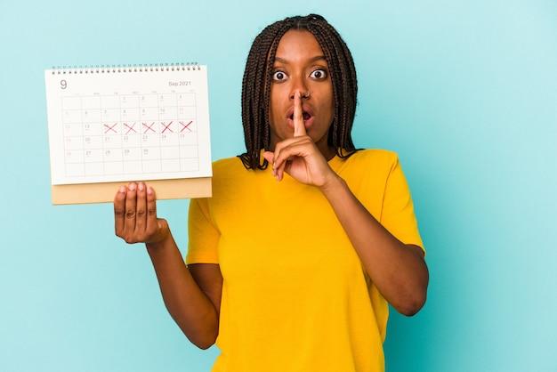 Jonge afro-amerikaanse vrouw met een kalender geïsoleerd op een blauwe achtergrond die een geheim houdt of om stilte vraagt.