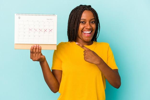Jonge afro-amerikaanse vrouw met een kalender geïsoleerd op een blauwe achtergrond glimlachend en opzij wijzend, iets tonend op de lege ruimte.