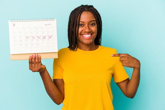 Jonge afro-amerikaanse vrouw met een kalender geïsoleerd op een blauwe achtergrond persoon die met de hand wijst naar een shirt kopieerruimte, trots en zelfverzekerd