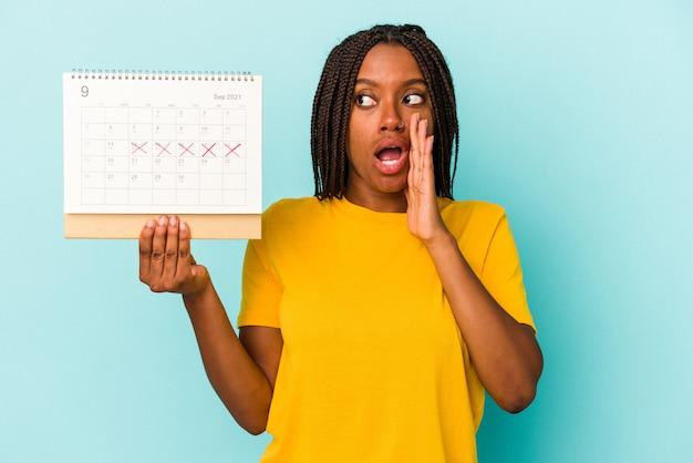 Jonge afro-amerikaanse vrouw met een kalender geïsoleerd op een blauwe achtergrond zegt een geheim heet remnieuws en kijkt opzij