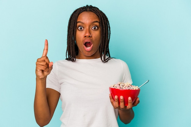 Jonge afro-amerikaanse vrouw met een kom cornflakes geïsoleerd op blauwe achtergrond met een geweldig idee, concept van creativiteit.