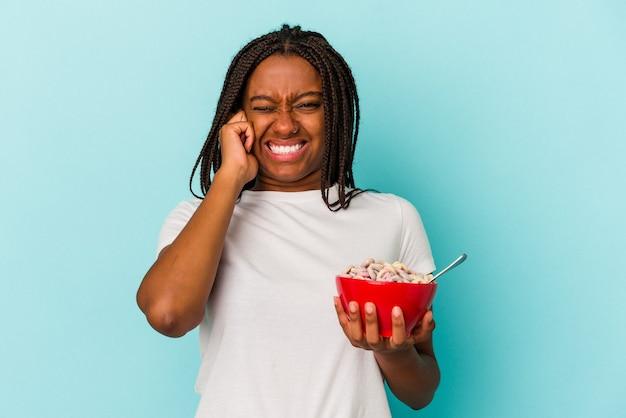 Jonge afro-amerikaanse vrouw met een kom cornflakes geïsoleerd op een blauwe achtergrond die oren bedekt met handen.